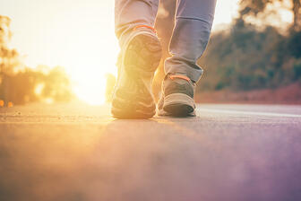bigstock-Man-Walking-On-Road-With-Sun-L-227539483