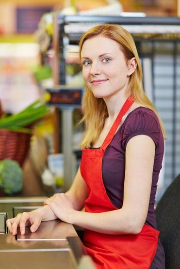 bigstock-Young-smiling-cashier-sitting--67719256-1